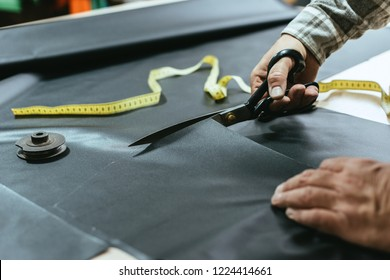 cropped image of male handbag craftsman cutting leather by scissors at workshop