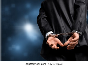 Cropped image of male hands in handcuffs behind his back