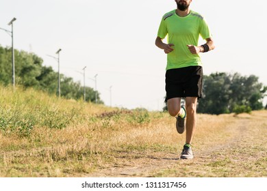 Cropped image of a male runner at field