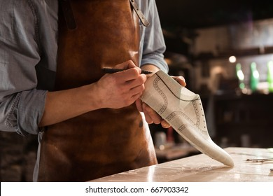 Cropped image of a male shoemaker making design for a new shoes at his workshop