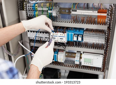 Cropped image of male technician repairing fusebox