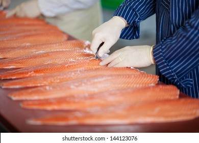 Cropped image of male workers cutting fishes with knife at table