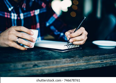 Cropped image of male's hands holding pen and writing down text information in notebook sitting indoors in cafe interior.Wooden table with cup of tasty coffee and notepad for noting some records