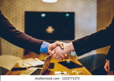 Cropped image of male's hands shaking in sign of making profitable deal for common business project,man agree in strategy of cooperation making contract for partnership in office during meeting