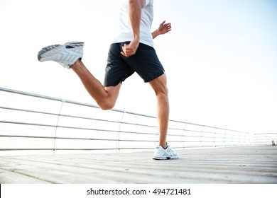 Cropped image of man athlete runner's feet and shoes running along beach pier