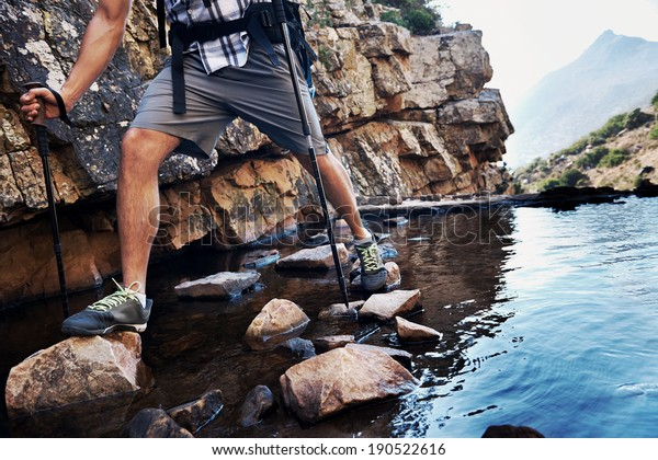 Cropped image of a man balancing on the rocks in the water he is trying to get across with copyspace