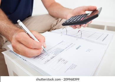 Cropped image of man calculating home finances at table