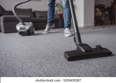 cropped image of man cleaning carpet in living room with vacuum cleaner