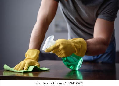 cropped image of man cleaning table in living room with spray bottle and rag
