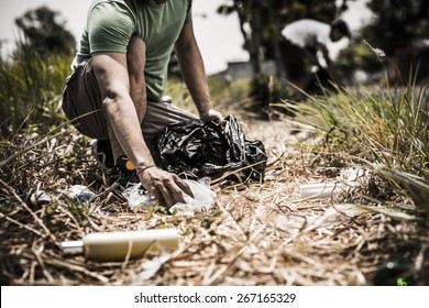 Cropped image of man collecting litter in forest