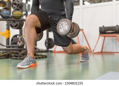 Cropped image of a man doing exercise for legs. Man working out legs with dumbbells. Healthy lifestyle and motivation concept.
