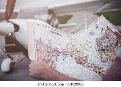 Cropped image of man holding the world map in hands while standing near private plane in airport. Choosing the next destination.