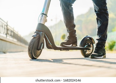 Cropped image of man in jeans and sneakers stepping on electric scooter while standing on city street