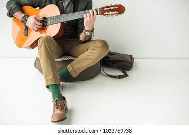 cropped image of man leaning on wall and playing acoustic guitar