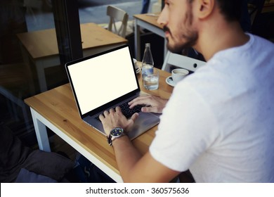 Cropped image of man learning on-line via laptop computer during lunch in cafe, male freelancer sitting in front open net-book with blank copy space screen for your text message or information content
