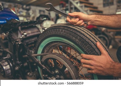 Cropped image of  man repairing a motorcycle in the repair shop