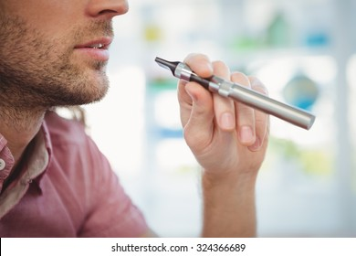 Cropped image of man smoking electronic cigarette in office