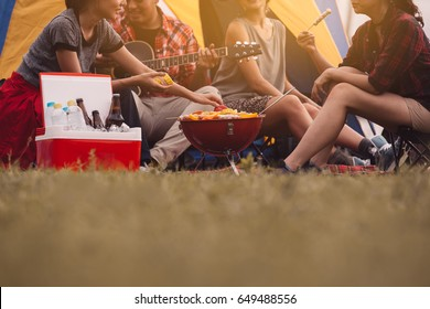 Cropped image of man and woman sitting in chairs outside the tent.Dinner party, Camping barbecue and roast pork ,vintage style ,Relaxation Fun Concept.