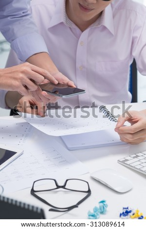 Cropped image of managers taking photo of business documents