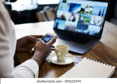 Cropped image of man's hand holding modern smartphone while sending multimedia files to laptop computer editing before publish with mock up screen connected to free wireless internet in coffee shop