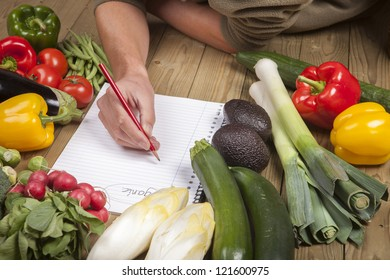 Cropped image of man's hand writing list of organic vegetables on wooden surface
