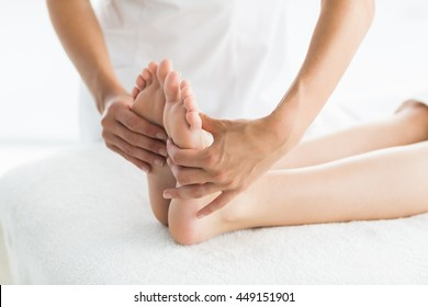 Cropped image of masseur giving foot massage to woman at spa