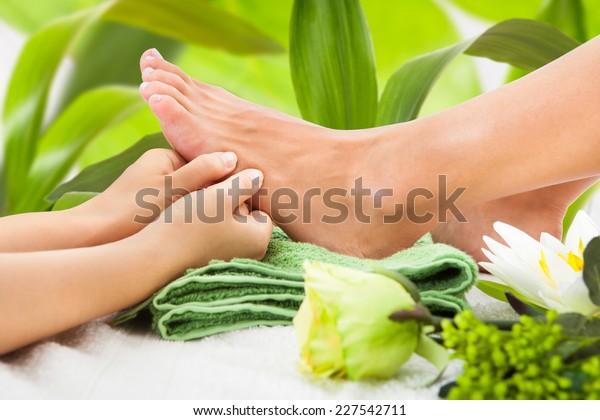 gepfropftes Bild von Masseuse Massage der Frau Fuß gegen Blätter im Spa-Bereich