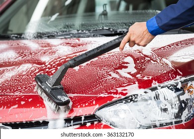 Cropped image of mature washer cleaning red car at service station