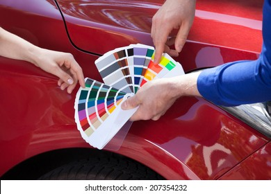 Cropped image of mechanic showing color samples to customer against car