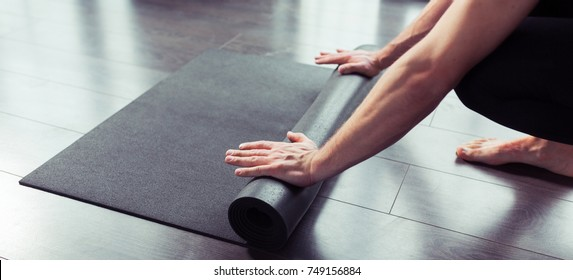 Cropped image of men hands rolling black yoga mat