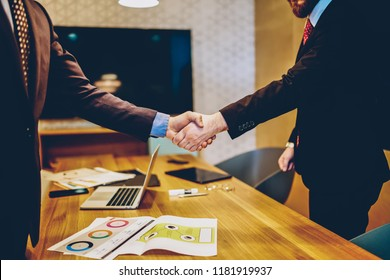 Cropped image of men in suits shaking hands making deal of sponsorship in business corporation, male entrepreneurs agree in partnership cooperation and contract during formal meeting in office