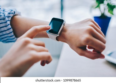 Cropped image of modern wearable computer on arm , using smartwatch for checking notification and data via wireless connection, finger on empty display of modern gadget with useful application