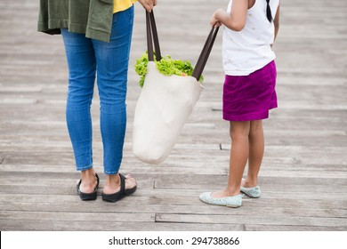 Cropped image of mother and daughter holding textile bag with groceries