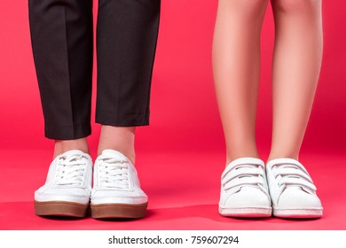 Cropped image of mother and daughter standing in gumshoes and sneakers on red