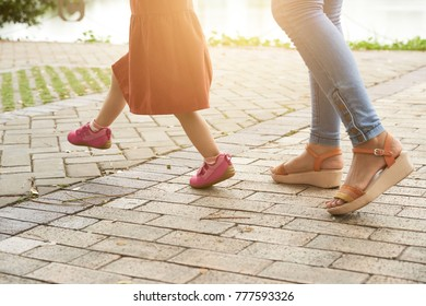 Cropped image of mother and daughter walking in the park together