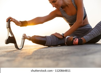 Cropped image of motivated disabled athlete woman with prosthetic leg doing stretching exercises while sitting at the beach