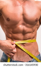 Cropped image of muscular man is measuring his waist with measuring tape.