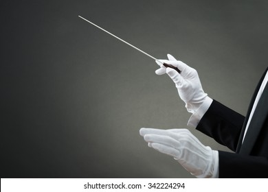 Cropped image of music conductor's hand instructing with baton against gray background