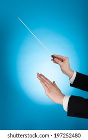 Cropped image of musician holding baton against blue background