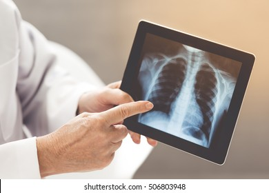 Cropped image of an old doctor in white medical coat showing X-ray picture on a tablet