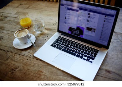Cropped image of open net-book with screen for information content or advertising text message, there is portable laptop computer, cup of coffee and glass of juice on wooden table in cafe interior