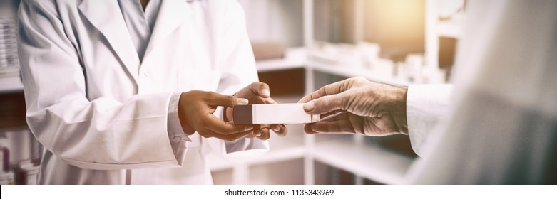 Cropped image of patient hand taking box from pharmacist at pharmacy