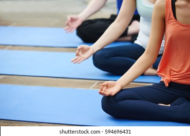 Cropped image of people practicing yoga in class