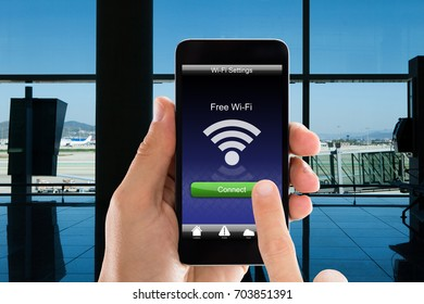 Cropped image of person's hands using free WiFi on smart phone in airport