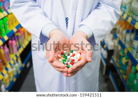 Cropped image of a pharmacist holding many colorful pills in the palms on the foreground