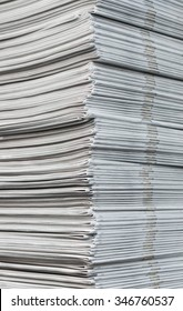 Cropped image of a pile of freshly printed newspapers hot off the press.