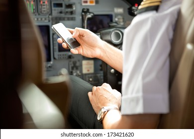 Cropped image of pilot using cell phone in private jet cockpit