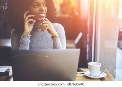 Cropped image of pondering smiling businesswoman looking away while thinking about successful ideas for personal startup project.Thoughtful positive hipster girl resting in coffee shop with gadgets