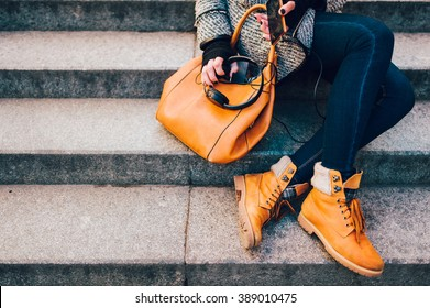 Cropped image of a portrait of stylish hipster girl sitting on the stairs. There are trendy yellow boots, bag, headphone and phone in a hand.