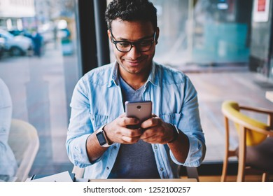 Cropped image of positive male person in glasses for better vision chatting with friends in social networks on smartphone.Mature happy man sending funny messages using application on cellular